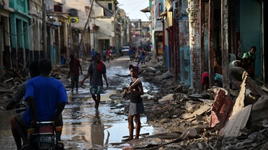 A girl walks on a street damaged in hurricane Matthew, in Jeremie, in western Haiti, on October 7, 2016.