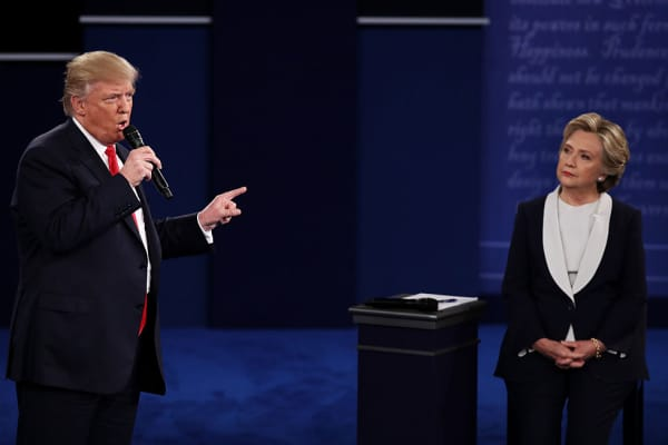 Republican presidential nominee Donald Trump (L) speaks as Democratic presidential nominee former Secretary of State Hillary Clinton looks on during the town hall debate at Washington University on October 9, 2016 in St Louis, Missouri