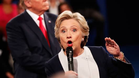 Democratic presidential nominee former Secretary of State Hillary Clinton (R) speaks as Republican presidential nominee Donald Trump looks on during the town hall debate at Washington University on October 9, 2016 in St Louis, Missouri