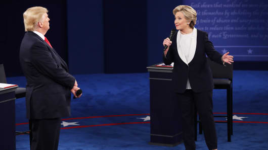 Democratic presidential nominee former Secretary of State Hillary Clinton (R) speaks as Republican presidential nominee Donald Trump listens during the town hall debate at Washington University on October 9, 2016 in St Louis, Missouri.