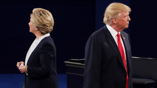 Democratic presidential nominee former Secretary of State Hillary Clinton (L) and Republican presidential nominee Donald Trump listen during the town hall debate at Washington University on October 9, 2016 in St Louis, Missouri.