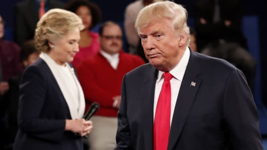 Republican presidential nominee Donald Trump and Democratic presidential nominee Hillary Clinton pause during their presidential town hall debate at Washington University in St. Louis, October 9, 2016.