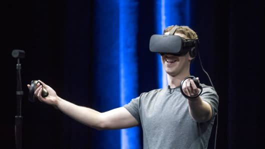 Mark Zuckerberg, chief executive officer and founder of Facebook Inc., demonstrates an Oculus Rift virtual reality (VR) headset and Oculus Touch controllers as the gives a demonstration during the Oculus Connect 3 event in San Jose, California.