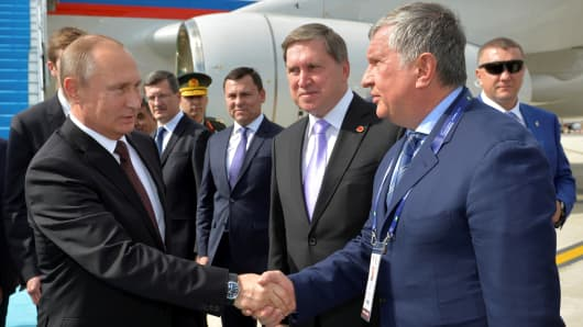 Russian President Vladimir Putin shakes hands with head of Russia's top oil producer Rosneft, Igor Sechin as he arrives at Ataturk airport in Istanbul, Turkey, October 10, 2016.
