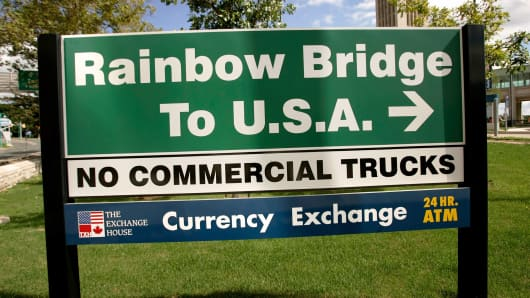 A sign on the Rainbow Bridge directs cars and buses to the U.S.A. in Niagara, Falls, Ontario.