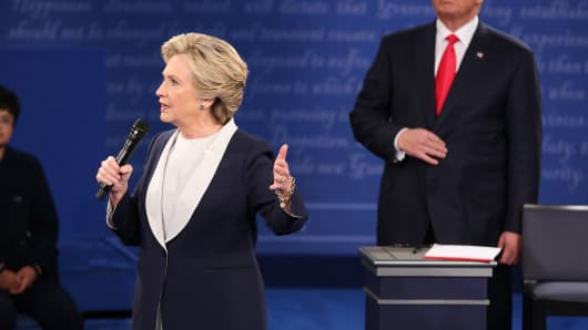 Hillary Clinton, 2016 Democratic presidential nominee, speaks as Donald Trump, 2016 Republican presidential nominee, stands during the second U.S. presidential debate at Washington University in St. Louis, Missouri, on Sunday, Oct. 9, 2016.