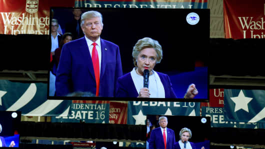 TV monitors in the press room show Republican nominee Donald Trump and Democrat nominee Hillary Clinton on stage as they participate in the 2nd debate at Washington University in St. Louis, Missouri October 9, 2016.