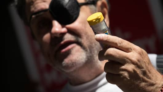Timothy Lunceford Stevens, who suffers from autoimmune diseases and allergies, holds up an EpiPen as he speaks during a protest against the price of EpiPens.