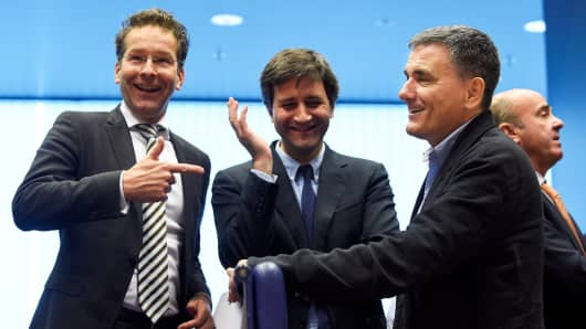 President of Eurogroup Jeroen Dijsselbloem (L) talks with Greek Finance Minister Euclid Tsakalotos (R) next to a Greek advisor during an Eurogroup meeting in Luxembourg.