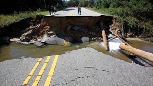 Residents inspect a washed-out section of collapsed road after Hurricane Matthew hit the state, in Fayetteville, North Carolina.