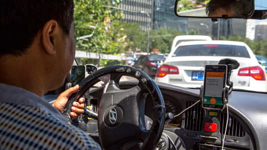 A taxi driver uses a taxi hailing app while driving.