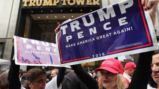 Defiant Donald Trump supporters gather outside of Trump Towers in Manhattan October 8, 2016 in New York City.