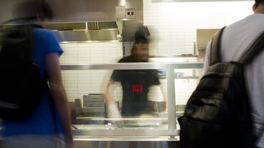 An employee serves customers in a Chipotle restaurant