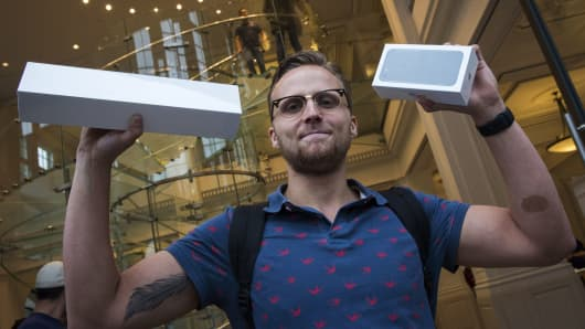 Dutch IT student Justin poses after having been the first customer to buy the new iPhone 7 during the opening sale launch at an Apple store in Amsterdam on September 16, 2016.