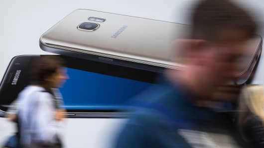 Pedestrians walk past a billboard advertising a Samsung Galaxy S7 Edge smartphone in London on October 11, 2016.