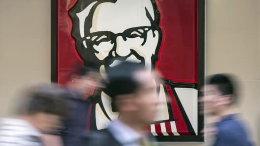 Pedestrians walk past a sign depicting Colonel Harland Sanders, the founder of Kentucky Fried Chicken, outside a Yum! Brands Inc. KFC restaurant in Shanghai, China.