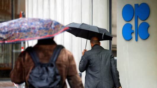 People carrying umbrellas walk by the Organization of the Petroleum Exporting Countries (OPEC) headquarters in Vienna, Austria.