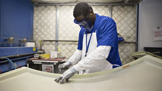 An employee sands the edge of a composite engine case part at the GE Aviation manufacturing facility in Batesville, Mississippi.