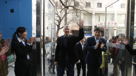 Tim Cook, Chief Executive Officer of Apple Inc., and China Mobile Chairman Xi Guohua (R) visit a China Mobile shop to celebrate the launch of iPhone 5S and iPhone 5C on China Mobile's fourth generation (4G) network on January 17, 2014 in Beijing, China.
