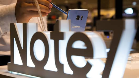 An employee uses a Samsung Electronics Co. S Pen stylus on a Samsung Galaxy Note 7 smartphone at one of the company's promotional booths in Seongnam, South Korea, on Wednesday, Oct. 5, 2016.