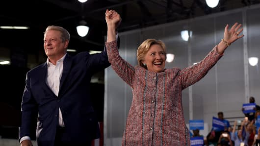 Former Vice President Al Gore (L) waves with Democratic presidential nominee Hillary Clinton during a climate change event at Miami Dade College-Kendall Campus in Miami, Florida October 11, 2016.