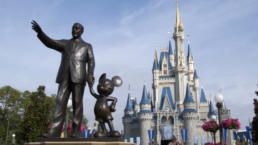 A statue of Walt Disney and Mickey Mouse stands in front of the Cinderella's castle at Walt Disney World's Magic Kingdom in Lake Buena Vista, Florida