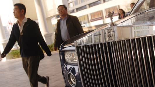 Pedestrians walk past a Rolls Royce parked in front of a Beijing hotel.