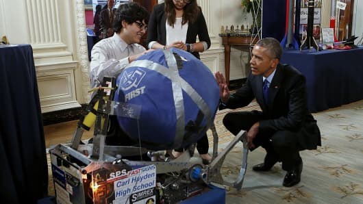 President Barack Obama (R) looks at the invention of Sergio Corral and Isela Martinez from Phoenix, Arizona, leaders of the robotics program from Carl Hayden High School during the 2015 White House Science Fair March 23, 2015 in Washington, DC.