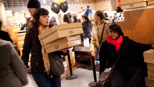 Customers carry boxes of UGG shoes while shopping in Tinton Falls, New Jersey.