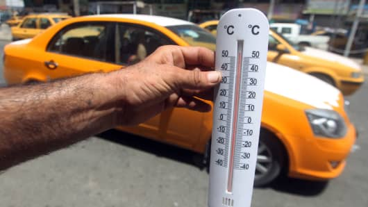 An Iraqi man shows a thermometer reading more than fifty degrees Celsius in the capital Baghdad.