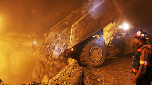 A dump truck unloads ore into a crusher in the underground area at Freeport McMoRan's Grasberg copper and gold mining complex in Papua province, Indonesia.