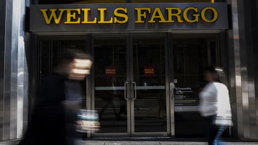 Pedestrians walk past a Wells Fargo & Co. bank branch in New York, U.S., on Thursday, Oct. 6, 2016.