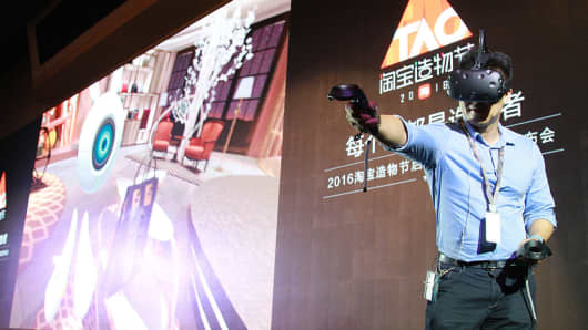 Zhuang Zhuoran, Senior Director for Alibaba Wireless Division, shows Alibaba's VR shopping technology Buy+ during the press conference on June 30, 2016 in Hangzhou, Zhejiang Province of China.