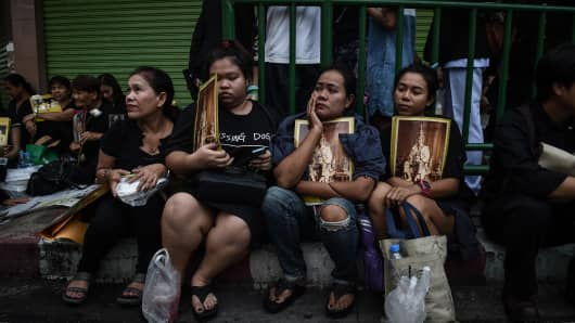 Mourners sit on the street with images of the late King Bhumibol Adulyadej outside Bangkok's Siriraj Hospita on October 14.
