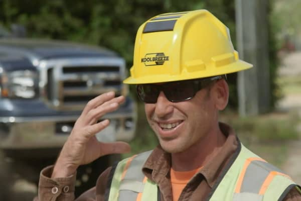 A construction worker tries on and provides feedback for the Kool Breeze solar helmet.