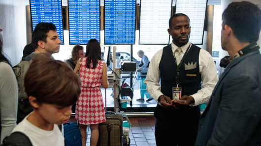 A Delta employee helps travelers near the Delta check-in counter at LaGuardia Airport.