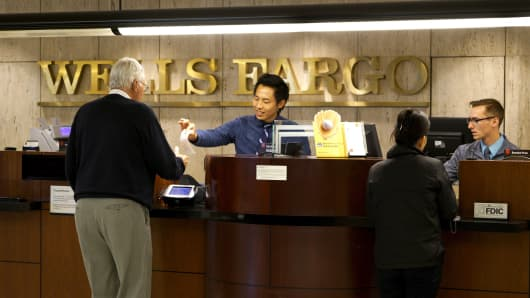 Tellers serve customers at the Wells Fargo bank in downtown Denver.