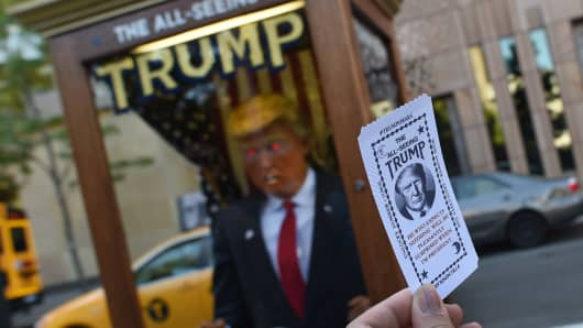 A woman shows her fortune card from a fortune-telling fairground attraction bearing the likeness of US Republican presidential candidate Donald Trump at Washington Square Park in New York on October 14, 2016.
