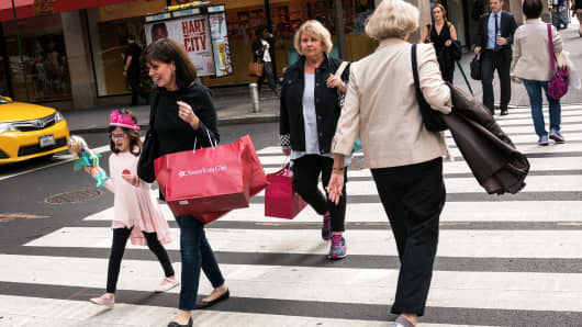 People carrying shopping bags walk along Fifth Avenue in New York.