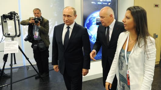 (L to R) Russia's President Vladimir Putin, Rossiya Segodnya general director Dmitry Kiselev and Russia Today (RT) television news editor-in-chief Margarita Simonyan.