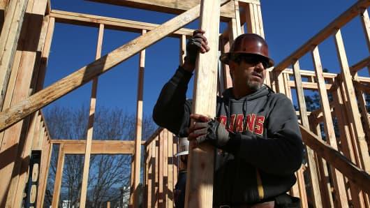 A worker carries lumber as he builds a new home in Petaluma, California.