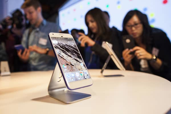 Members of the media examine Google's Pixel phone during an event to introduce Google hardware products on October 4, 2016 in San Francisco, California.