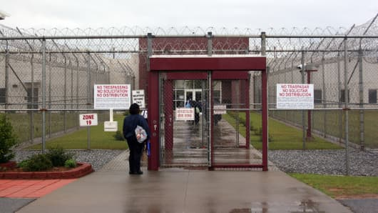 An employee waits at the front gate of the Stewart Detention Facility, a Corrections Corporation of America immigration facility in Lumpkin, Ga.