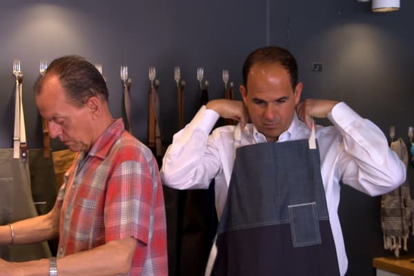Marcus Lemonis tries on a Tilit apron, which he thinks can boost the credibility of Bowery's textile department.