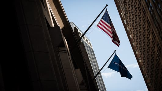 An American and a Deutsche Bank AG flag fly outside the company's office on Wall Street in New York.