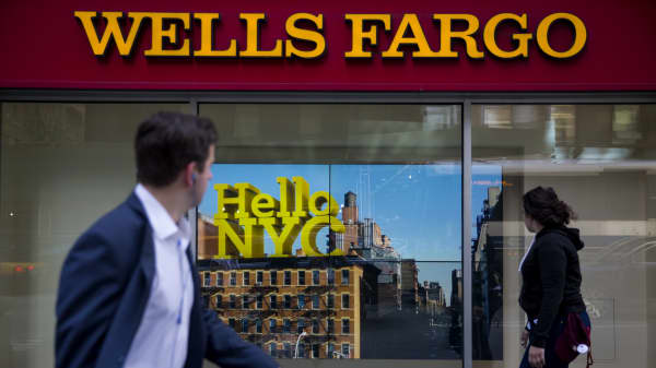 Pedestrians pass in front of a Wells Fargo & Co. bank branch in New York.
