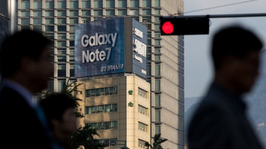 An advertisement for the Samsung Electronics Co. Galaxy Note 7 smartphone stands on display behind a red traffic light in Seoul, South Korea, on Wednesday, Oct. 12, 2016.