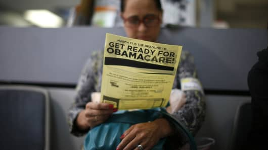 A woman reads a leafleft on Obamacare at a health insurance enrollment event