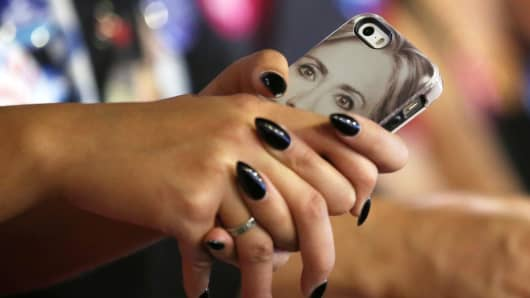 A woman holds a mobile phone with a case featuring a picture of Hillary Clinton, as she listens to her speak at a rally in Las Vegas, Nevada, October 12, 2016.