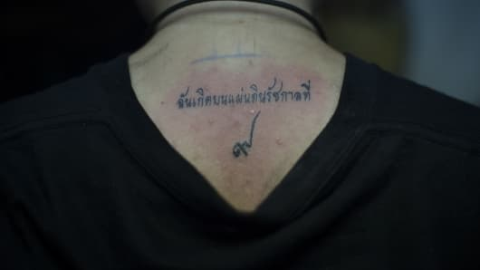 A customer gets a tattoo in honour of the late Thai King Bhumibol Adulyadej at Tattoo OD Studio in Bangkok. The tattoo reads 'I was born in the reign of King Rama IX', referring to King Bhumibol Adulyadej as the 9th king of the Chakri Dynasty.